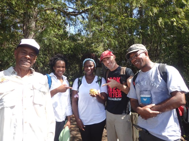 Outdoor Afro hikers check out an orange discovered along the trail.